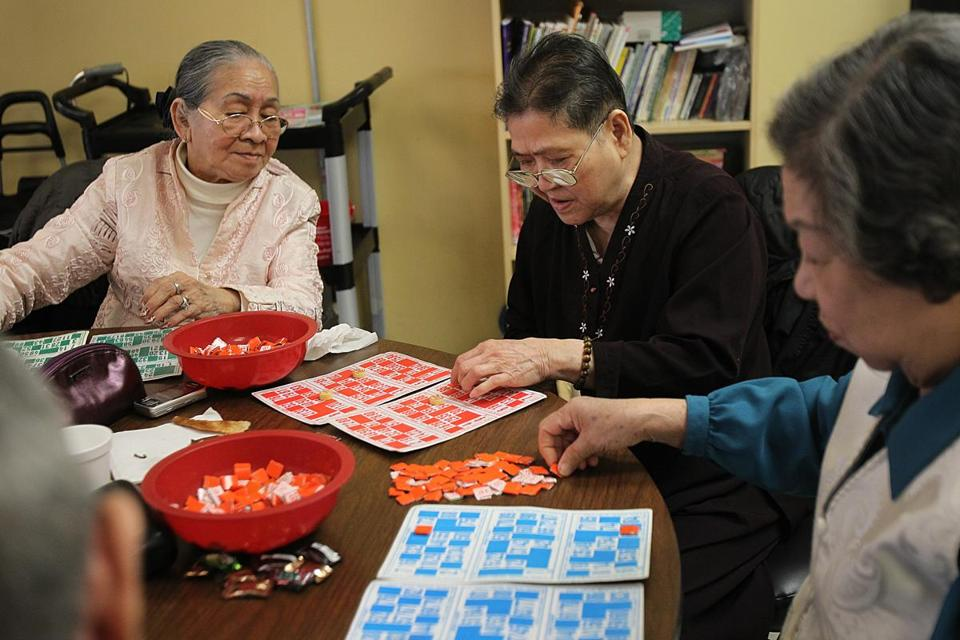 From left, Du Nguyen, Phai Nguyen, and Anh Nguyen focus their attention on a game of bingo.